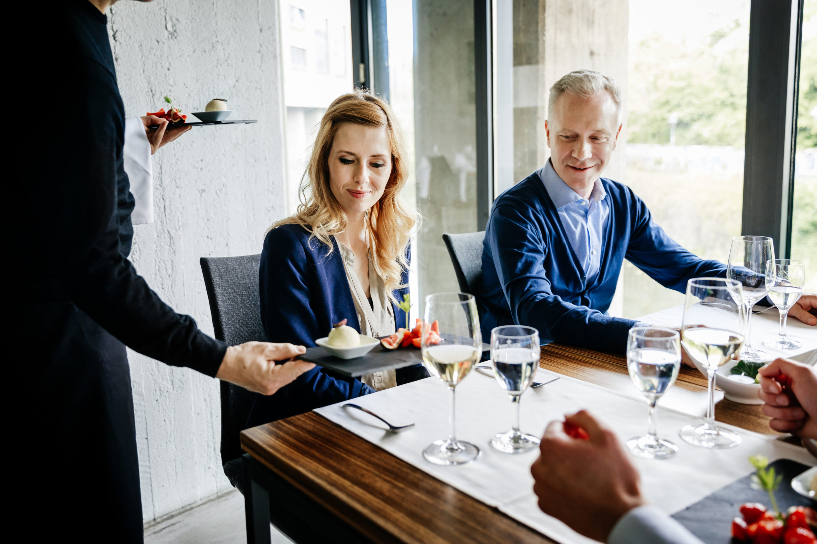 A waiter is serving food to a group of business colleagues having lunch together.